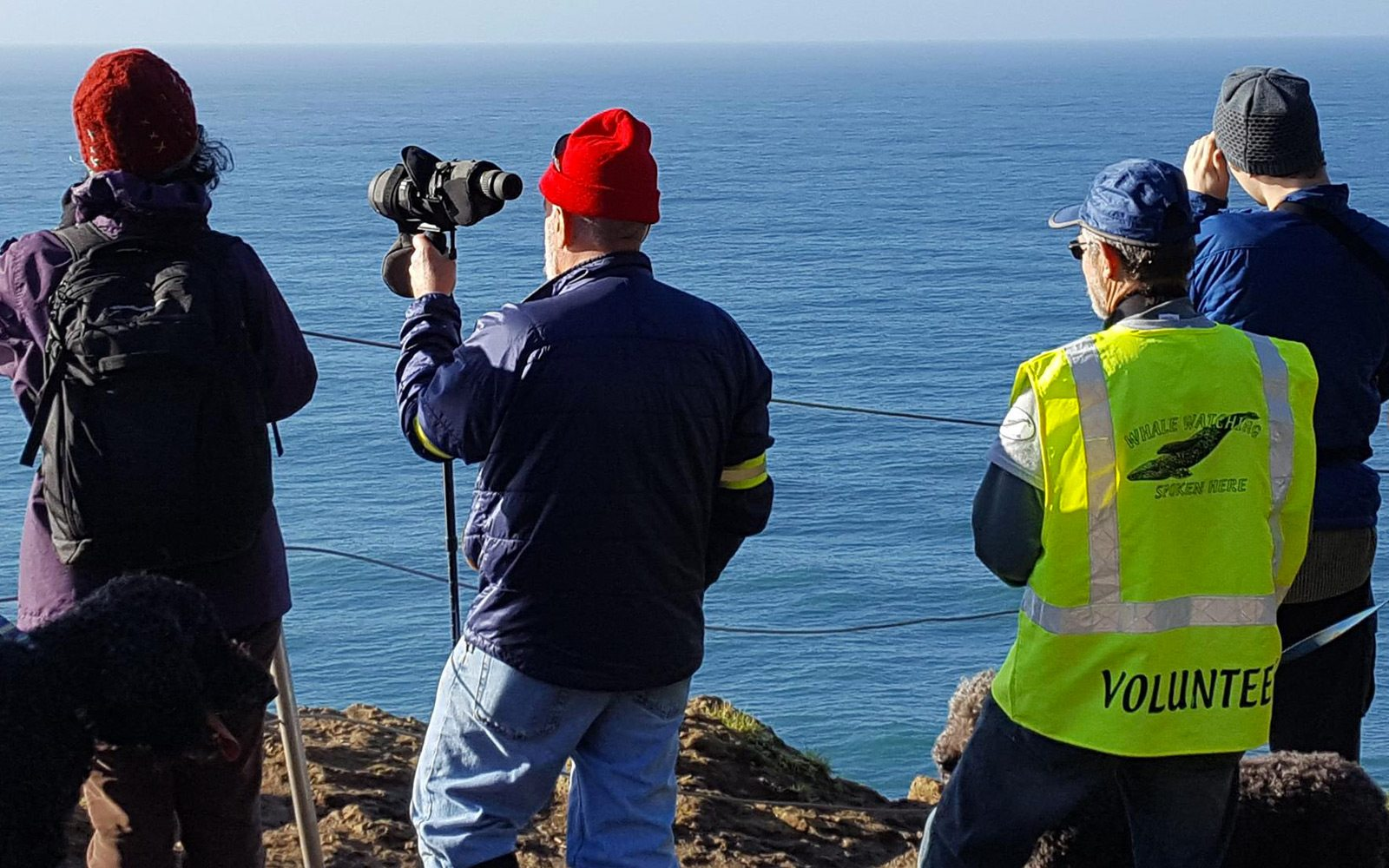 A volunteer assists those watching whales at an unknown location along the Oregon Coast.